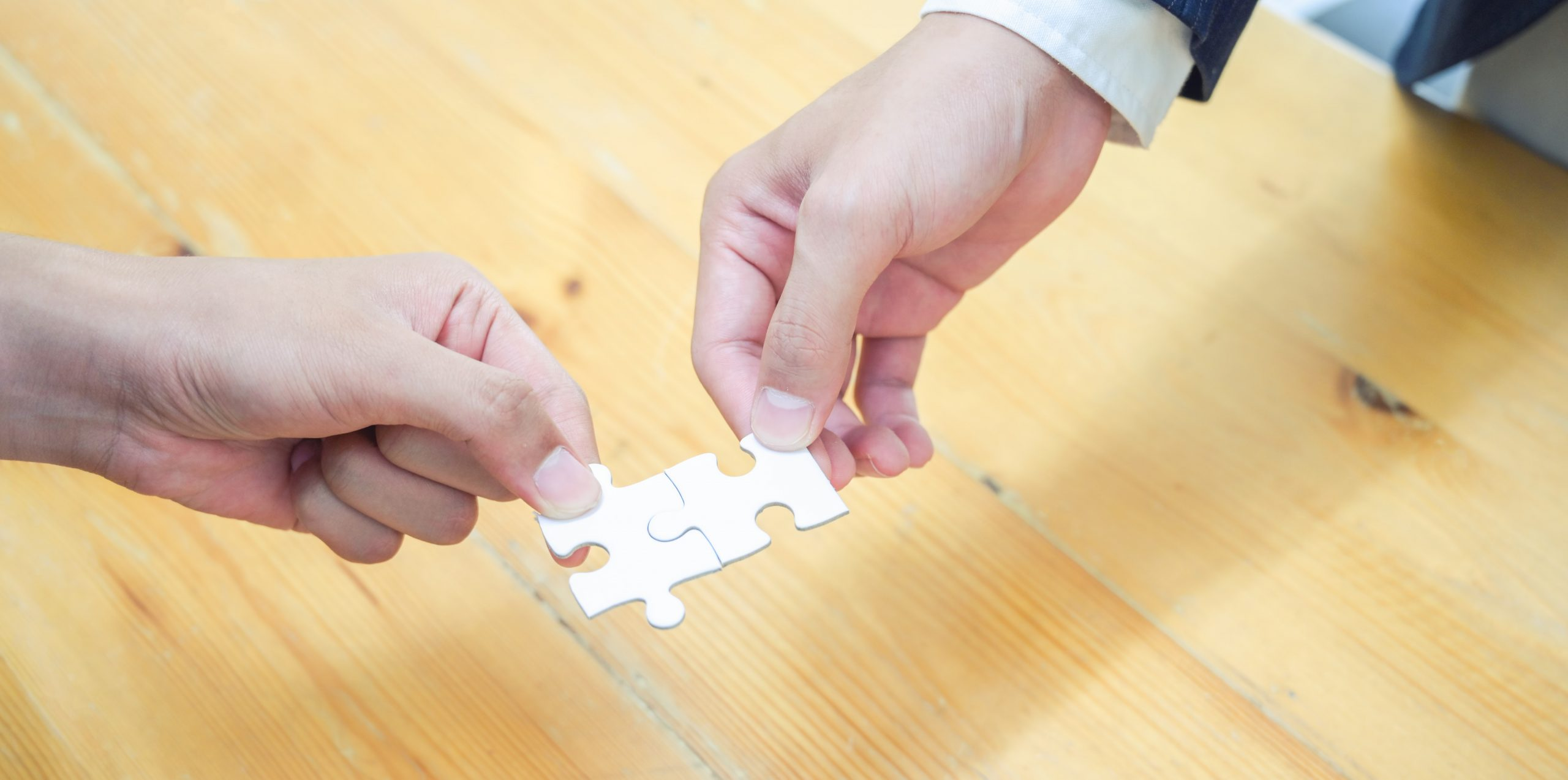 Jigsaw pieces being placed together representing first aid, first aid for mental health and wellbeing coming together in our holistic wellbeing programmes
